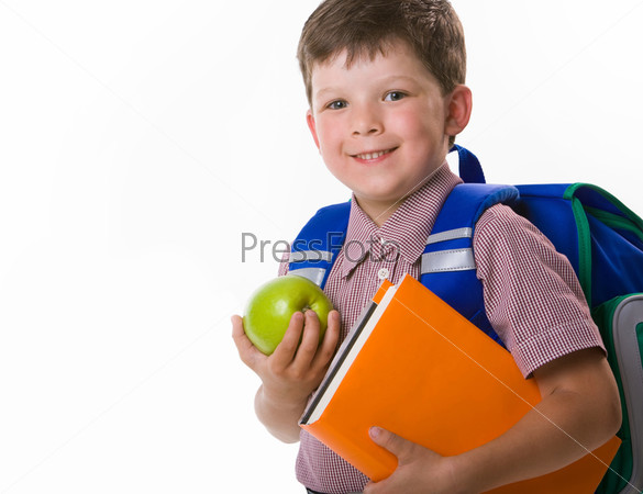 Счастливый школьник с яблоком и учебниками в руках