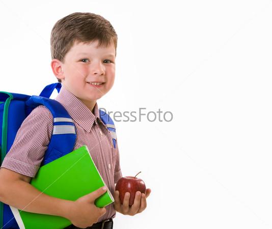 Радостный ученик с зеленой тетрадью и красным яблоком в руках