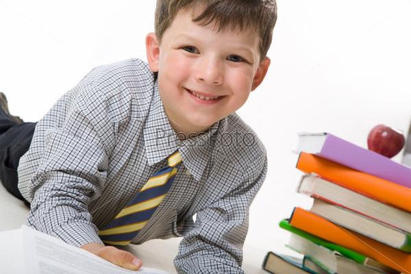 Радостный школьник лежит на полу с раскрытой тетрадью