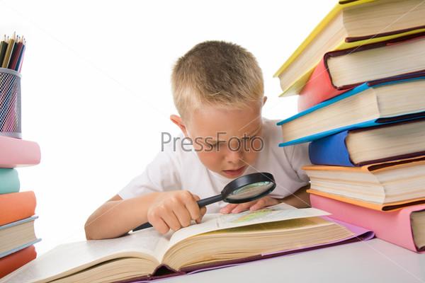 Мальчик рассматривает под лупой изображение в книге