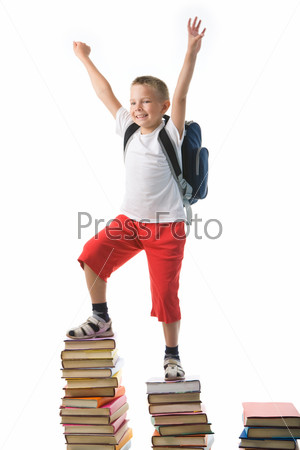 Эмоциональный школьник стоит на груде учебников подняв руки вверх