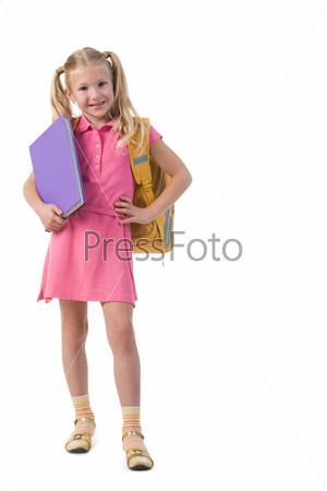 Девочка с рюкзаком и книгой в руках смотрит в камеру и улыбается