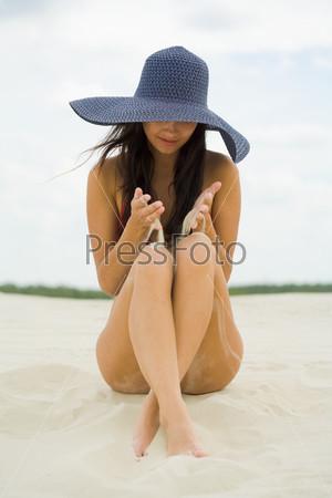 Девушка в большой синей шляпе сидит на пляже и сыпет песок на колени