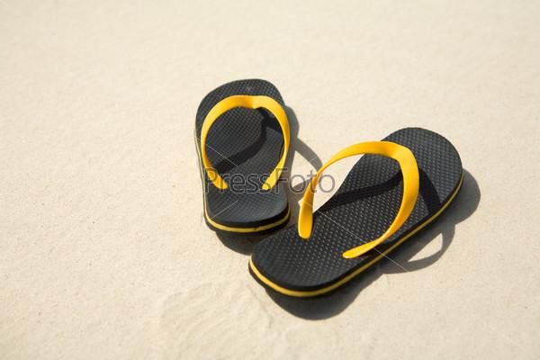 Крупный план пляжной обуви на песке
