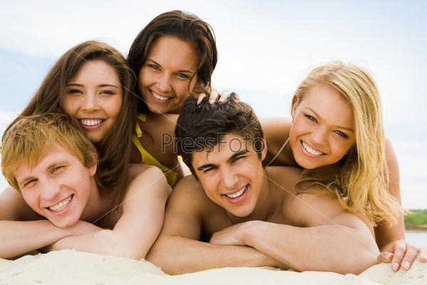 Дружная молодежная комапния лежит на песке