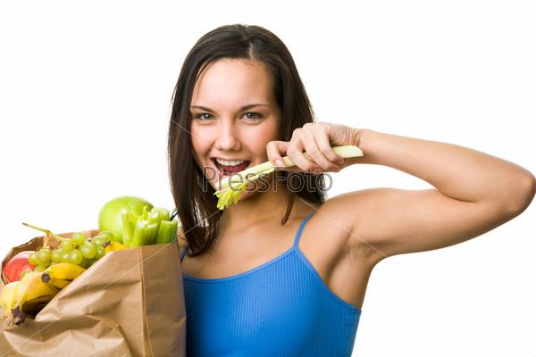 Симпатичная девушка держит пакет с фруктами и овощами и ест сельдерей
