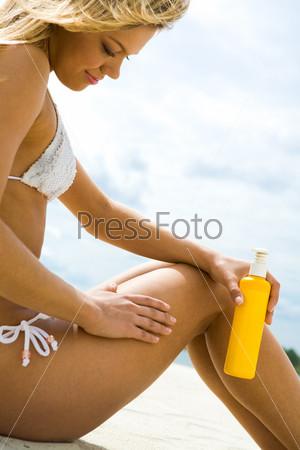 Девушка сидит на песке и наносит крем на кожу
