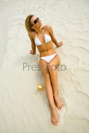 Вид сверху красивой блондинки лежащей на песке