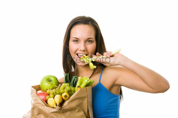Симпатичная девушка с пакетом фруктов и овощей ест сельдерей и улыбается