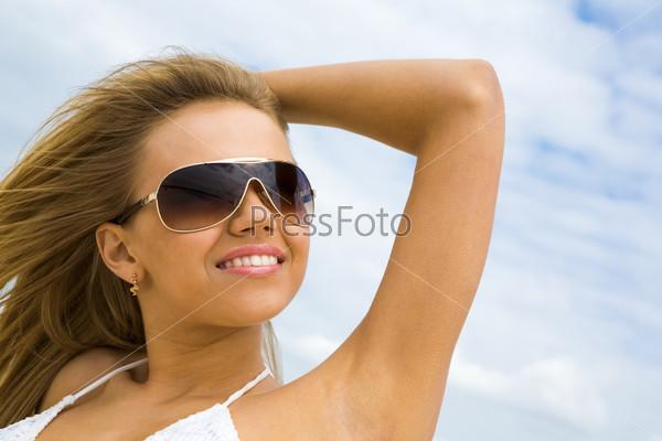 Красивая девушка в солнцезащитных очках стоит с улыбкой на фоне неба