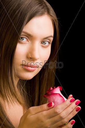 Красивая брюнетка с розой в руке на черном фоне