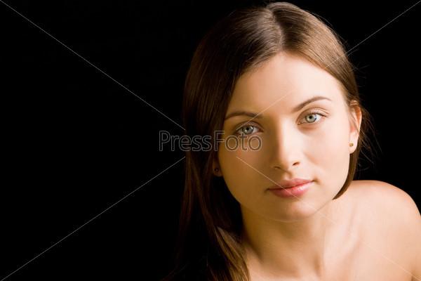 Очаровательная девушка загадочно смотрит в камеру