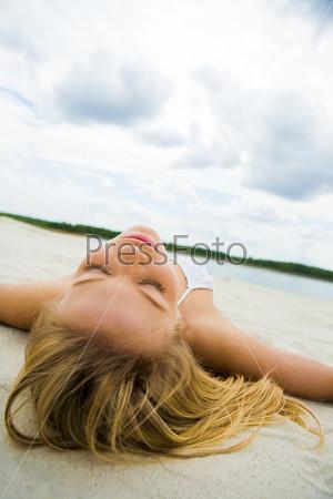 Фотография на тему Девушка загорает на песке на берегу озера