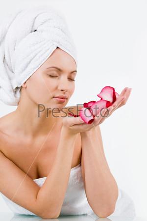 Милая девушка наслаждается запахом лепестков розы на ладонях