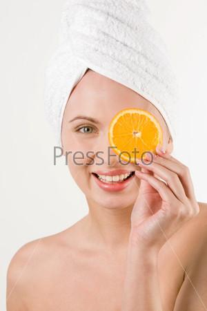 Девушка с полотенцем на голове закрывает один глаз кусочком апельсина