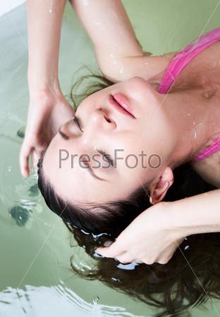 Спокойная девушка с закрытыми глазами окунает волосы в ванну с водой