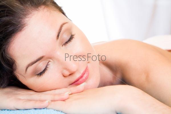 Красивая женщина лежит с закрытыми глазами в спа салоне