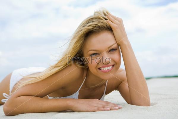 Красивая девушка лежит на песке и с улыбкой смотрит в камеру