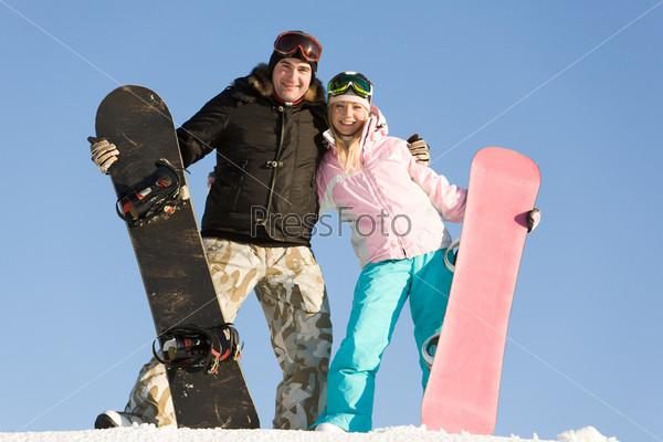 Радостная пара стоит на снегу с досками для сноуборда