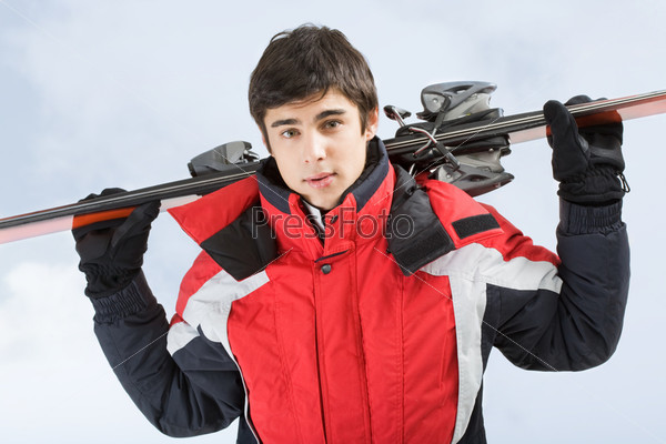 Привлекательный молодой человек держит на спиной лыжи