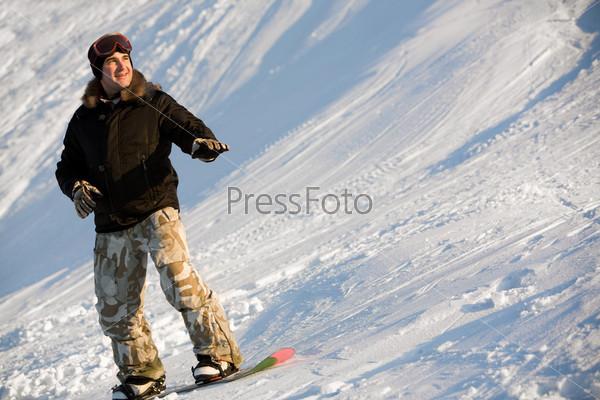 Мужчина стоит на доске для сноуборда на зимнем курорте