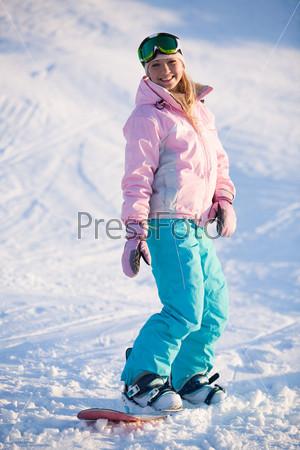 Счастливая девушка катается на сноуборде на лыжном курорте зимой