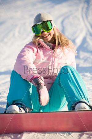 Девушка в костюме сноубордиста сидит на снегу и смеется