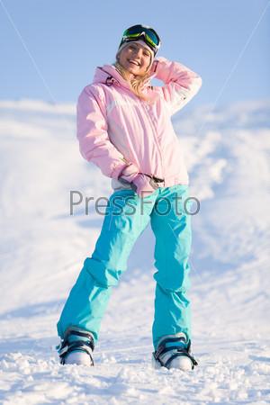 Девушка в спортивной одежде стоит на снегу и улыбается