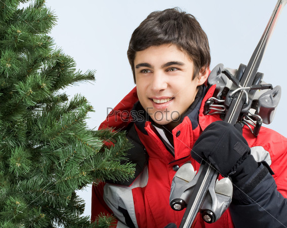 Привлекательный молодой человек с лыжами в руках стоит около хвойного дерева