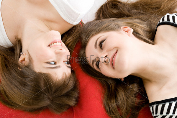 Two girls lying on red pillow