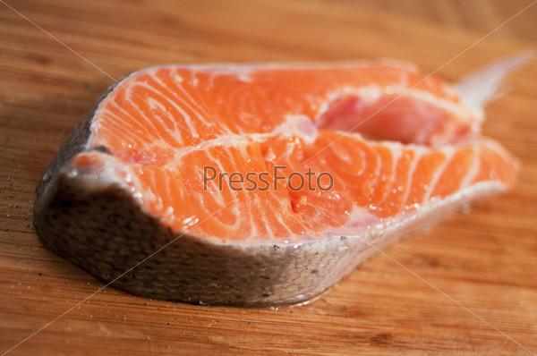 Кусок сырой горбуши на деревянном столе