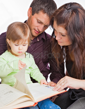 Mother, fathher and little daughter reading book