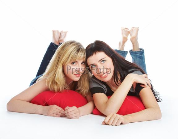 Две подруги лежат на красных подушках и разговаривают