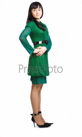 Девушка в зеленом платье стоит на белом фоне