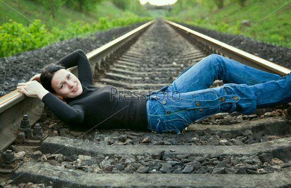 Young girl lying on the railway