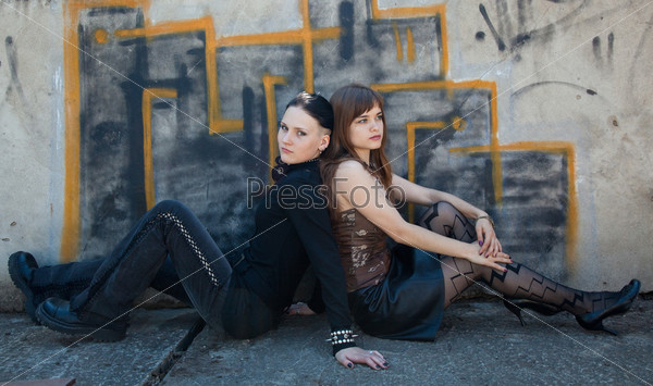 Girls sitting in front of graffiti wall
