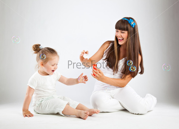 Little girl and her mother blowing bubbles