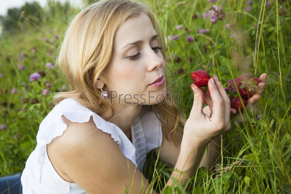 Young blond woman eating strawberries