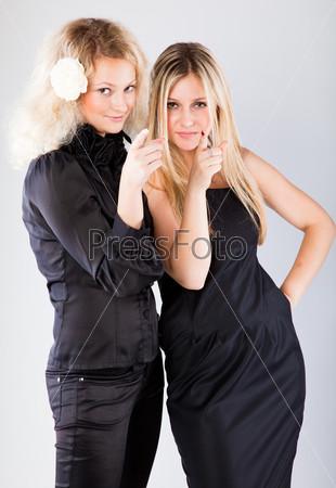 Две стильные блондинки указывают в камеру