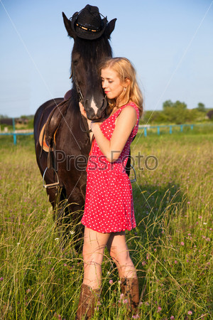 Young blond woman in red dress  with horse