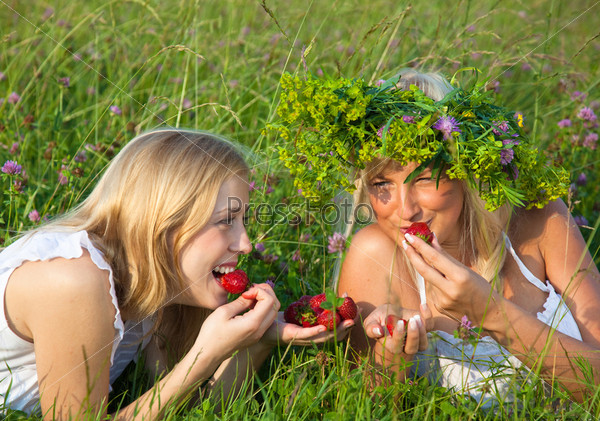 Two young blond women  eating strawberries