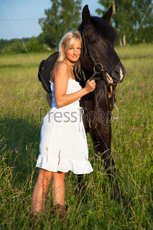 Young blond woman in white dress with horse