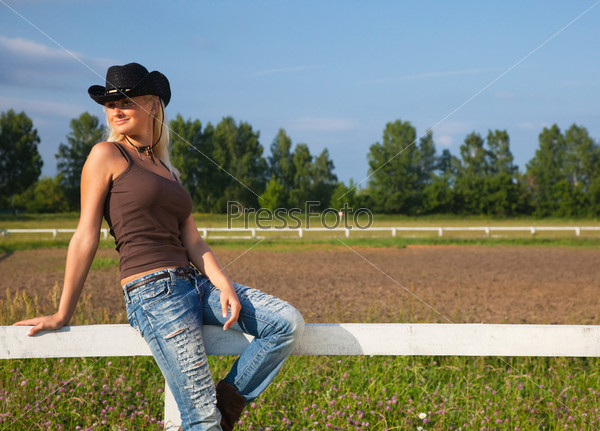 Young cowgirl sitting on a fence