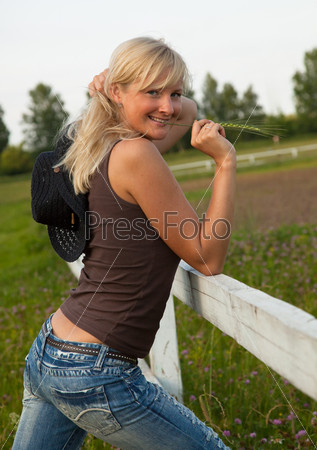 Young cowgirl stand near a fence