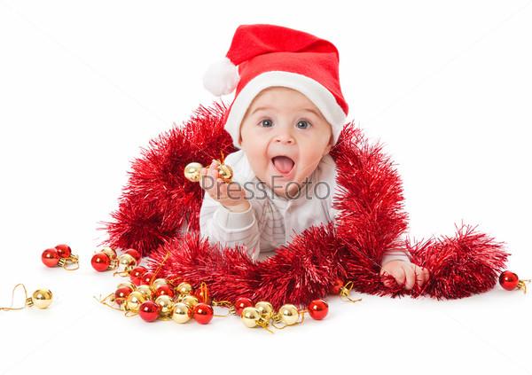 Радостный малыш в красном колпаке с елочными игрушками и мишурой
