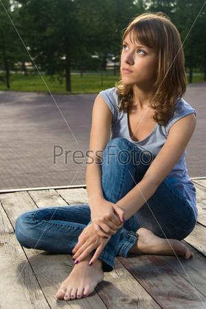 Девушка сидит в джинсах и босиком