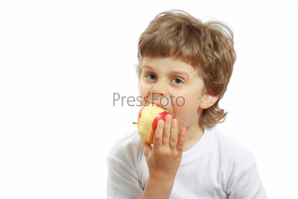 Маленький мальчик ест яблоко