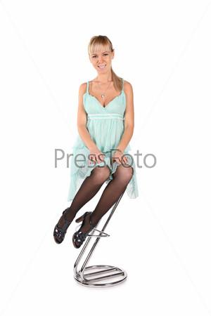 Девушка в платье на барном стуле на белом фоне