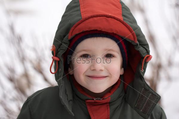 Портрет улыбающегося мальчика в шапке и куртке на улице