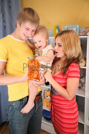 Счастливый отец держит маленького сына на руках, рядом стоит удивленная мама